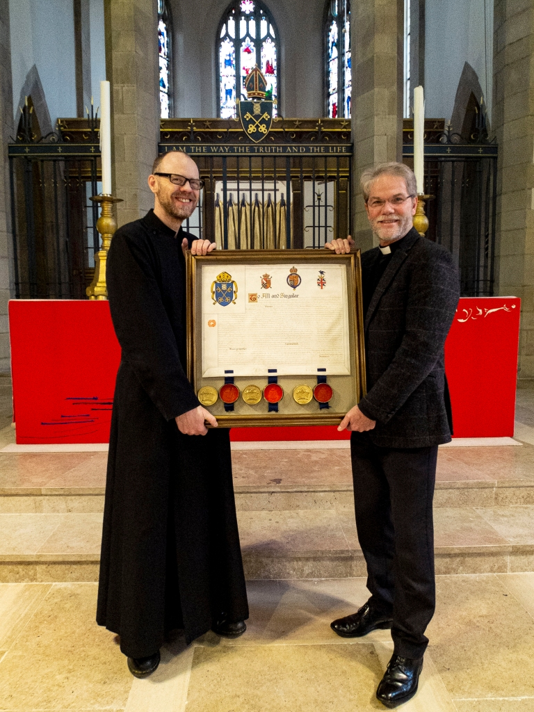 Text Box: Head Verger David Worsley and Dean Jerry Lepine holding the refurbished charter, which will be viewable on the day.